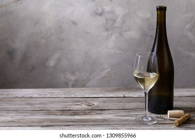 wine in wineglass with bottle and bung on old grey wooden table.