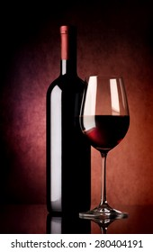 Wine in wineglass and bottle on vinous background