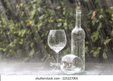 A winebottle and two glasses on a garden table during heavy summer rain