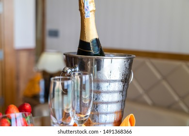 Wineglass and a bottle of chilled champagne are in an ice bucket for welcoming guests in hotel