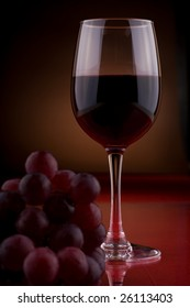 a wineglass and bunch of grapes on the table