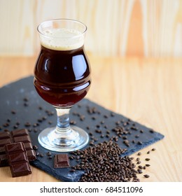 Wineglass of chocolate beer serving on black rock with chocolate and barley. Beverage background with a copy space.