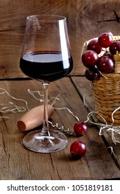 wineglass next to grapes on a basket on a rustic wooden background