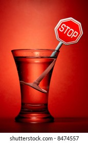Wineglass with stop sign over red background