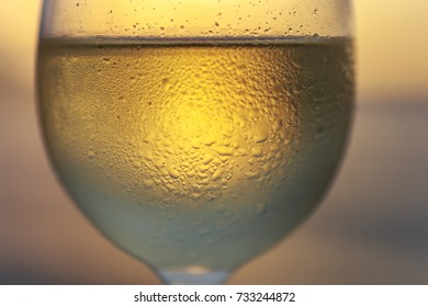 Wineglass of white wine at sunset dramatic sky background. Closeup. Travel vacations concept.
