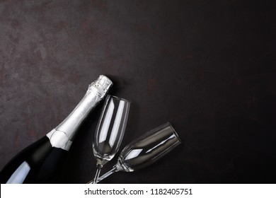 Wineglasses and bottle of champagne with serpentine lying on black wooden background. New Year celebration concept. Top view. Flat lay.