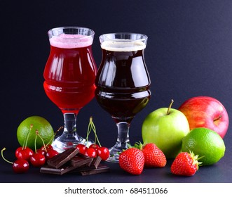 Wineglasses of craft beer with an assortment of fruits and berries over a black background. Beverage background with a copy space.