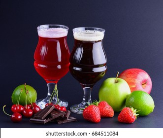 Wineglasses of craft sweet beer with an assortment of fruits and berries over a black background. Beverage background with a copy space.