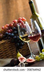 wineglasses of red, rose and white wine ,bottle, grapes in wicker basket and figs on brown wood textured table covered with canvas towel