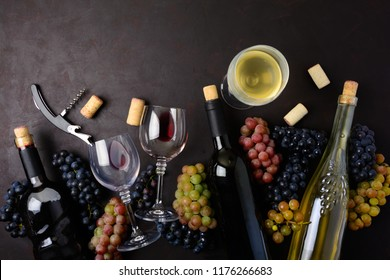 Wineglasses with red and white wine, bottles, grapes, corkscrew and corks lying on dark wooden background. Top view. Flat lay. Copy space