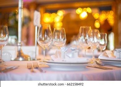 Wineglasses stand side by side on white dinner table