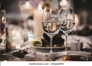 Wineglasses with water stand behind white plates on the dinner table