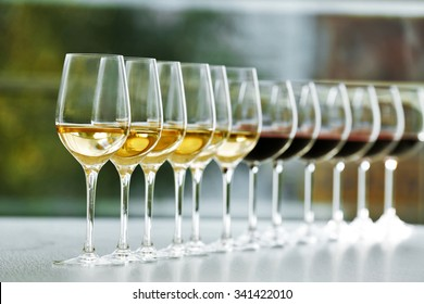 Wineglasses with white and red wine on wooden table on bright background