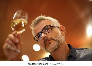 Winemaker tasting white wine in cellar