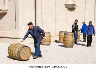Winemakers move barrels with wine in  Castel Mimi Wine Resort at day, BULBOACA, MOLDOVA. 05-10-2018