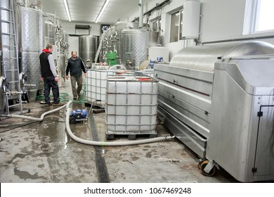 Winemakers in wine production connecting the hose to the fermenting unit.. Stainless steel tanks for a fermentation on background. Modern manufacture of winemaking.