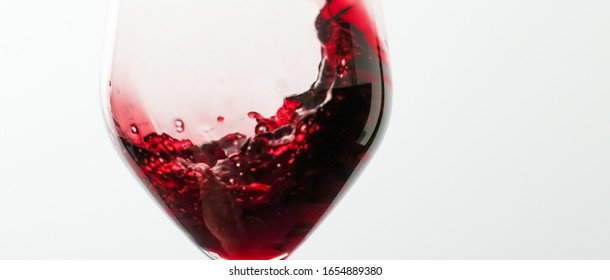 Winery, cheers and winemaking concept - Glass of red wine, pouring drink at luxury holiday tasting event, quality control splashing liquid motion background for oenology or premium viticulture brand