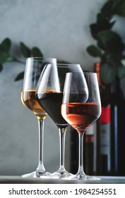 Wines assortment. Red, white, rose wine in wineglasses and bottles on gray background. Wine bar, shop, tasting concept