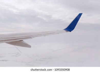 wing of aircraft flying above snowy land