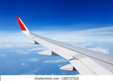 Wing of the aircraft on the background of clouds and bright blue sky. copy space