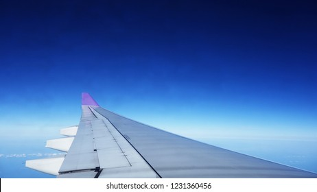 The wing of an airplane above the clouds. Wing of an airplane flying above the morning clouds. view from the window of an airplane flying