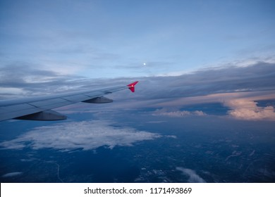 Wing of an airplane after sunset with the moon on the sky