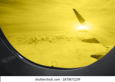 Wing of an airplane among beautiful long river in the porthole in yellow-gray color 2021