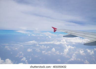 wing of airplane among cloudy blue indigo sky