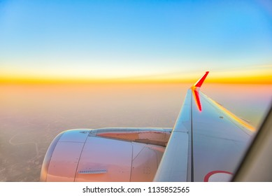 Wing of an airplane flying above the clouds at sunset