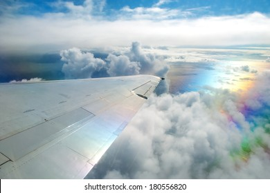 Wing of airplane flying above clouds in the sky and with a view of the ocean in background