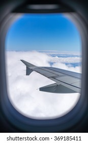 Wing of an airplane flying above the clouds. people looks at the sky from the window of the plane, using air transport to travel.