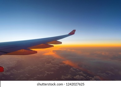 Wing of an airplane flying above the morning clouds with sky at twilight time from the window in traveling concept.