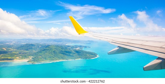 Wing of an airplane flying above the ocean. The view from an airplane window. Photo applied to tourism operators.