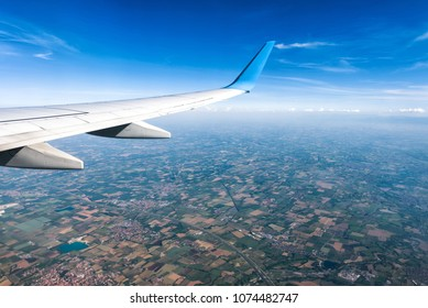 Wing of an airplane flying above villages or countryside. The plane's wing on the blue sky and earth background. Aerial panoramic view of motley land from airplane window. Travel concept.