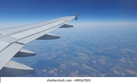 wing of airplane and landscape during flight