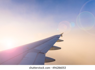 Wing of the airplane on blue and pink sky background