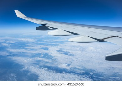 wing of airplane over cloudy blue sky in Europe on morning sun light, determine to transport ion airline vacation for spring summer holiday.