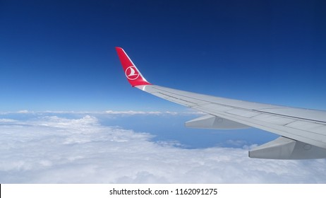 Wing of Boeing 737 Turkish Airlines, clouds and blue sky. Bologna, Italy - July 26, 2018