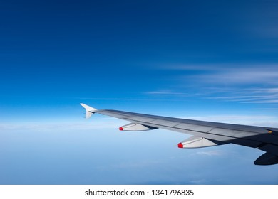 Wing of a commercial plane while flying above the clouds with a clear blue sky