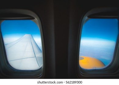 The wing with engine on the background of cloud. View from porthole