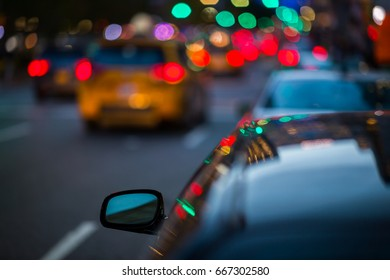 Wing mirror of a car in busy city traffic
