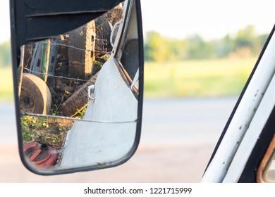 wing mirror reflection in a junkyard