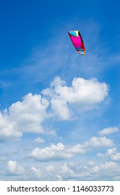 wing of a parachute against a blue sky with clouds in a brights