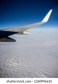 Wing of the passenger plane flying in high altitude above the clouds