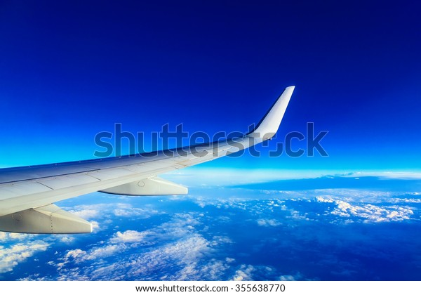 Wing of Plane at Blue Sky Background above Clouds