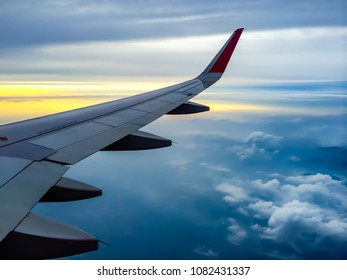 Wing of the plane with cloudy sky on background at sunset