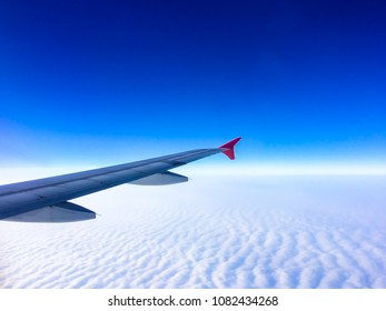 Wing of the plane with cloudy sky on background