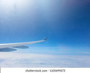 Wing of the plane on blue sky background with the morning sun light and copy space