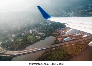 Wing of the plane on blue sky background with brige view down