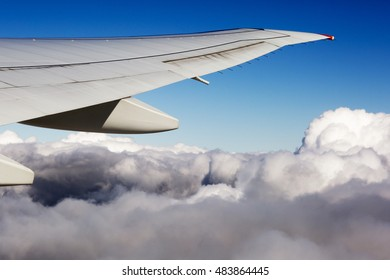 The wing of the plane on sky background. Aerial view of thick clouds over the land, the landscape.